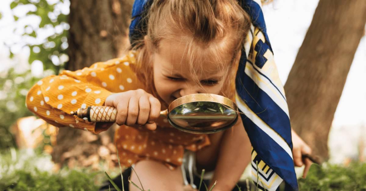 Outdoor Preschool Activities - preschool girl looking through magnifying glass.